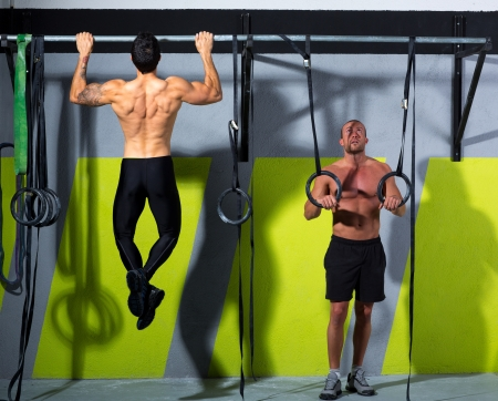 Crossfit dip ring and toes to bar man pull-ups men workout at gym photo