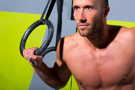 Crossfit dip ring man relaxed after workout at gym dipping exercise photo