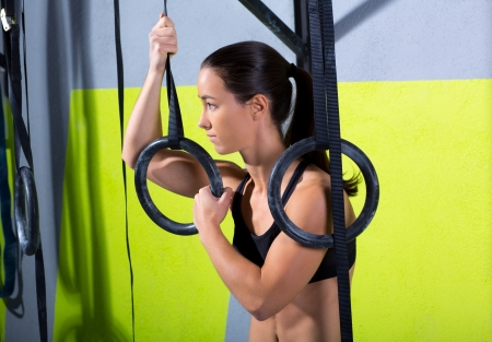 pull up: Crossfit dip ring woman relaxed after workout at gym dipping exercise Stock Photo