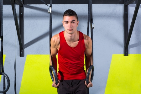 cross bar: Crossfit dip ring young man workout at gym dipping exercise