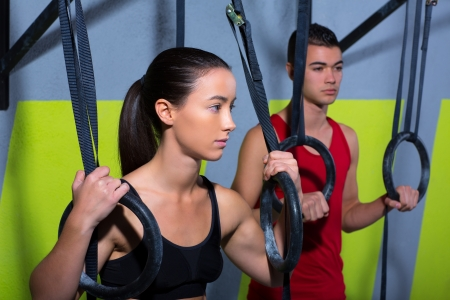 cross bar: Crossfit dip ring man and woman relaxed after workout at gym dipping exercise