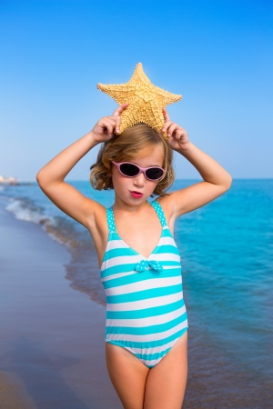 child swimsuit: child kid girl in summer beach vacations with starfish and aqua sea