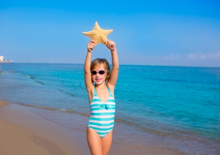 child kid girl in summer beach vacations with starfish and aqua sea photo