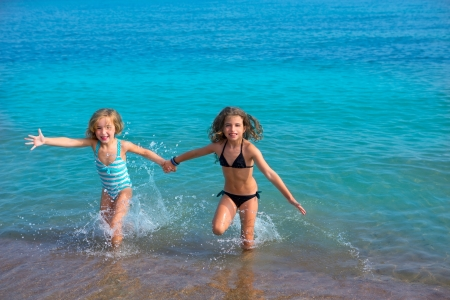 children girls friends running together in the beach shore on summer vacation photo
