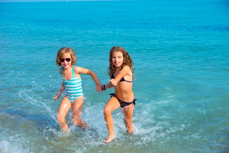 young girl bikini: children girls friends running together in the beach shore on summer vacation