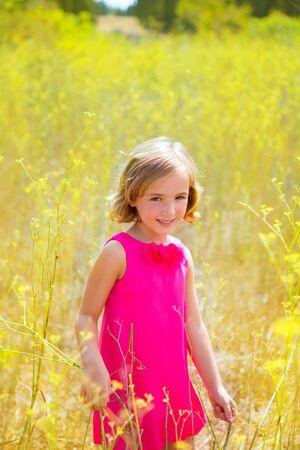 mediterranean forest: child kid girl in spring yellow flowers field and pink dress in Mediterranean forest