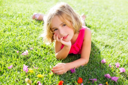 blond kid girl lying relaxed in garden grass with flowers smiling photo