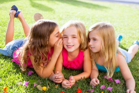 children friend girls group playing whispering on flowers grass in vacations Reklamní fotografie