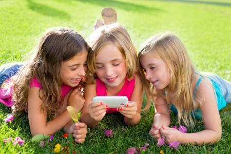 children friend girls group playing internet with mobile smartphone on grass photo