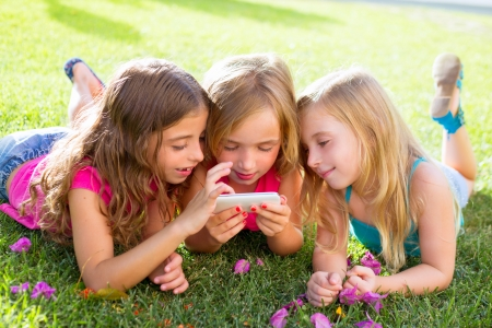 woman smartphone: children friend girls group playing internet with mobile smartphone on grass