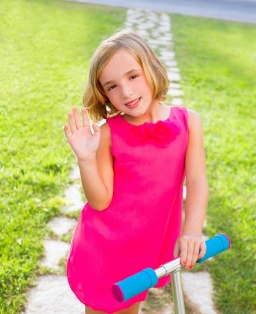 child happy girl playing with scooter in garden happy greeting hand gesture Stock Photo - 17237577