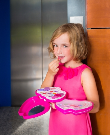 little girl dress: child kid girl playing with makeup lipstick in the lift door smiling happy