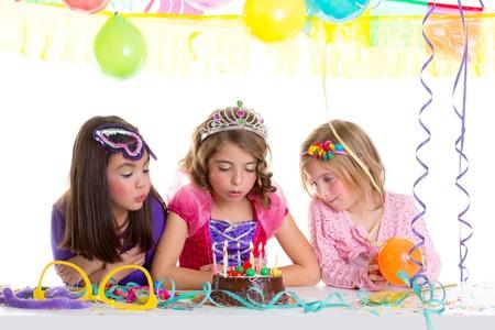 kids dress: children happy girls blowing birthday party chocolate cake candles Stock Photo