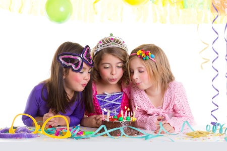 party dress: children happy girls blowing birthday party chocolate cake candles Stock Photo
