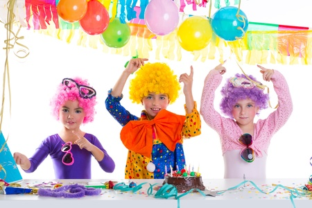Children happy birthday party with clown wigs and chocolate cake photo