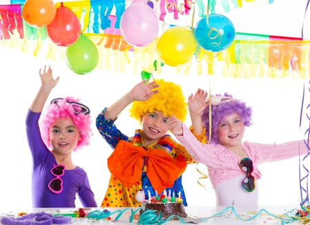 children celebration: Children happy birthday party with clown wigs and chocolate cake