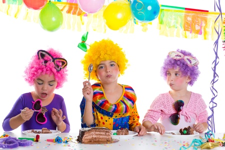 Children happy birthday party eating chocolate cake with clown wigs photo