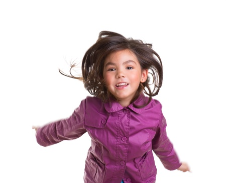 Asian child girl jumping happy with winter purple coat moving hair on white photo