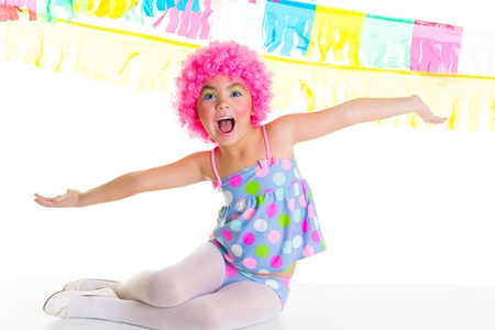child kid girl with party clown pink wig funny happy open arms expression and garlands photo