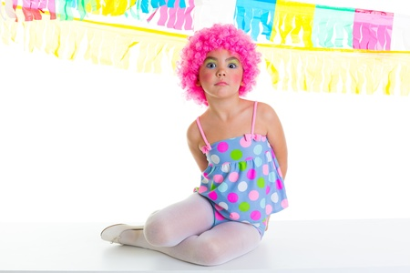 child kid girl with party clown pink wig funny expression and garlands photo