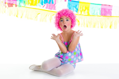 child kid girl with party clown pink wig funny surprise gesture and garlands photo