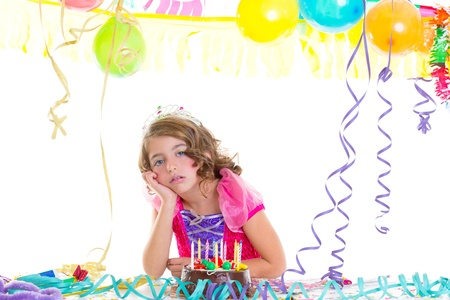 child sad kid crown princess in birthday party bored gesture and chocolate cake photo