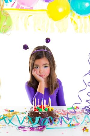 asian child kid girl in birthday party bored sad gesture and chocolate cake photo