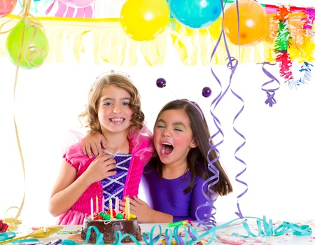 children happy hug in birthday party laughing with baloons garlands and candles cake photo