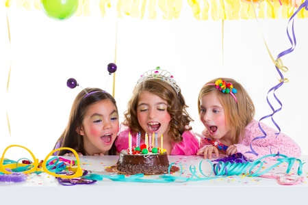 fancy dress party: children kid girls birthday party looking excited chocolate candles cake