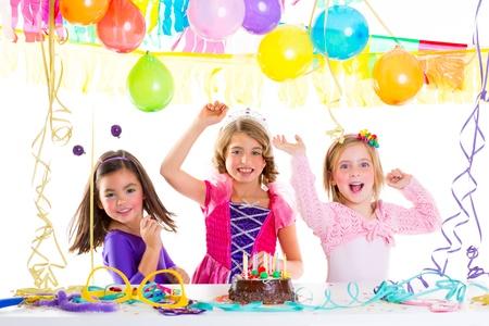 coronas de princesa: kid ni�os en la fiesta de cumplea�os bailando feliz riendo con globos serpentinas y guirnaldas Foto de archivo