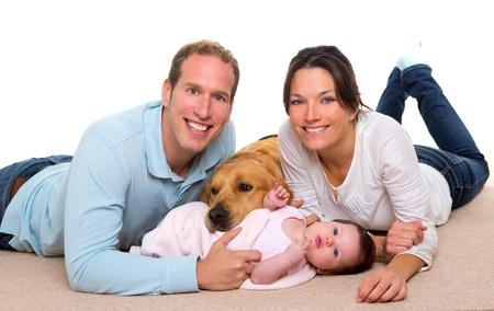 puppy love: Beb� madre y padre de familia feliz con el perro perdiguero de oro en la alfombra