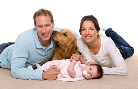 Baby mother and father happy family with golden retriever dog on carpet photo