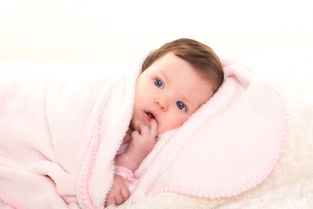 baby girl with toothache in pink with winter white fur background
