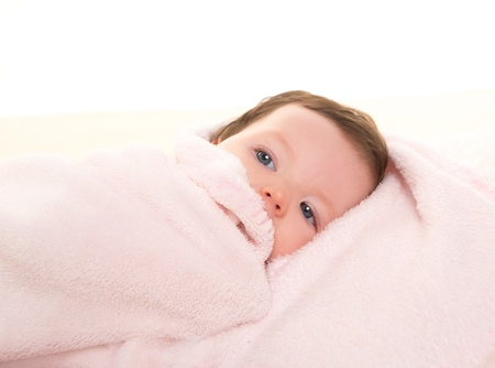 baby girl under hidden pink blanket on winter white fur background photo