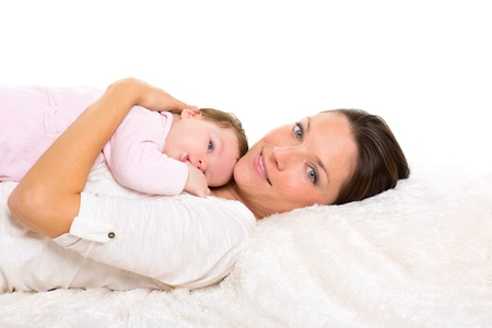 Baby girl and mother lying happy together on white fur blanket photo