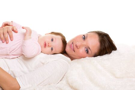 Baby girl and mother lying happy together on white fur blanket Stock Photo - 17237656