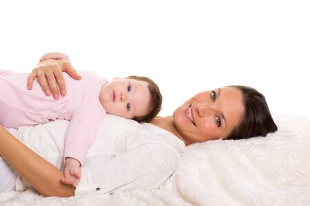 helpmate: Baby girl and mother lying happy together on white fur blanket Stock Photo