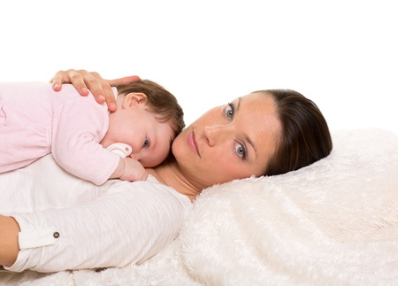 Baby girl and mother lying together on white fur almost sleeping with pacifier photo
