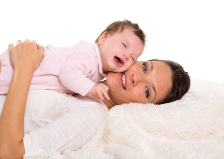 Baby girl crying and mother lying together on white fur blanket Stock Photo - 17237632