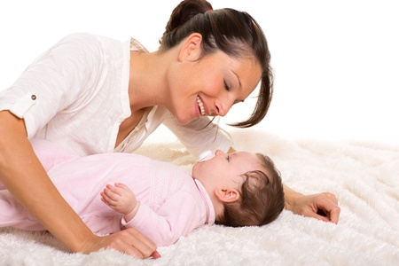 Baby girl and mother lying happy playing together on white fur blanket Stock Photo - 17237592