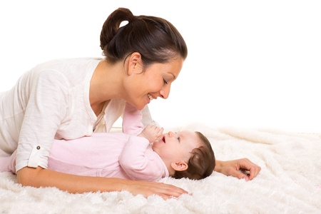 Baby girl and mother lying happy playing together on white fur blanket Stock Photo - 17237639