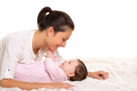 helpmate: Baby girl and mother lying happy playing together on white fur blanket Stock Photo