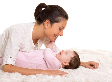 Baby girl and mother lying happy playing together on white fur blanket photo