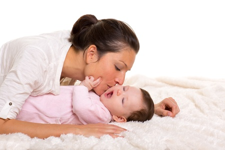 Baby girl and mother kissing her lying happy on white fur blanket Stock Photo - 17237615