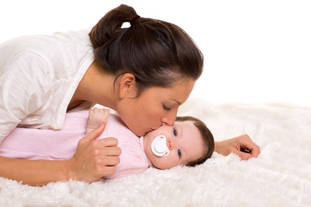 Baby girl and mother kissing her lying happy on white fur blanket Stock Photo - 17237601