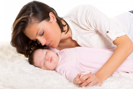 Baby girl sleeping with mother care near on white fur photo