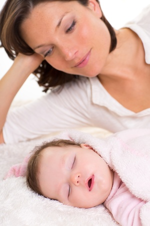 Baby girl sleeping with mother care near on white fur Stock Photo - 17237620