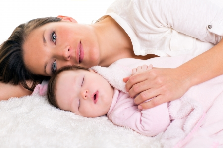 comforter: Baby girl sleeping with mother care near on white fur Stock Photo