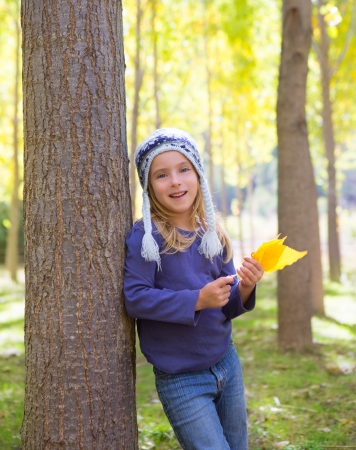 beautiful blonde girl with green eyes: Child girl in autumn poplar forest with yellow fall leaves in hand smiling happy outdoor