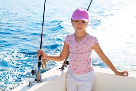 child girl sailing in fishing boat holding rod in blue sea photo